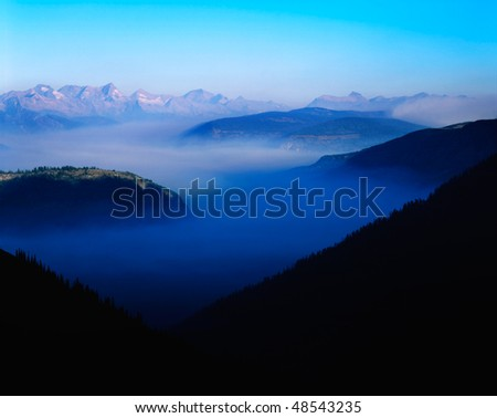"""Forest Fire Smoke Amid The Peaks, Glacier National Park, Montana, Along The """"Going To The Sun Road"""" - stock photo"""