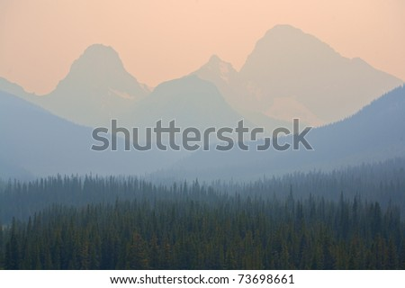 Forest fire smoke in the Rocky Mountains of Alberta - stock photo