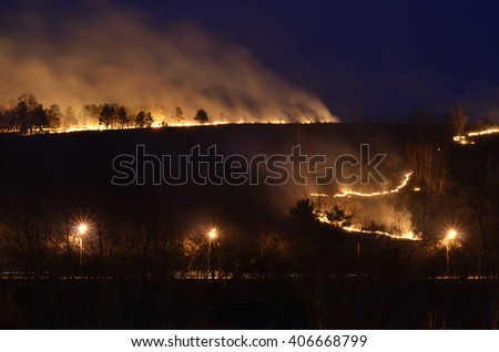 Forest fires in the city. Pine Forest in the city on fire. Thick smoke is a sign of extinguishing. Firemen is working  there. Novokuznetsk, Kemerovo region, Russia. - stock photo