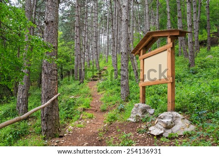 Forest footpath with wooden sign board ready to put information. Path included for the blank area. - stock photo