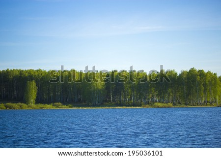Forest lake under blue cloudy sky. Lake forest clouds. - stock photo