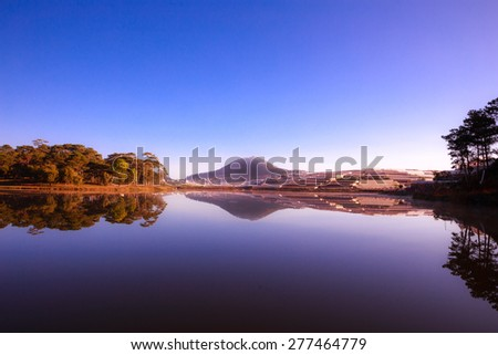 Forest lake under blue cloudy sky. Than Tho lake, Da lat, Vietnam. Da lat is one of the best tourism city in Vietnam. Dalat city is Vietnam's largest vegetable and flowers growing areas. - stock photo