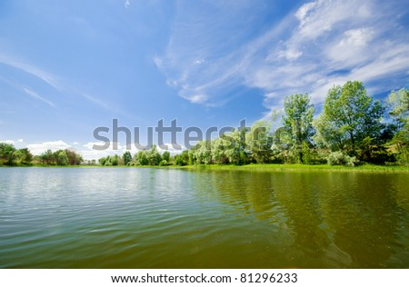 Forest lake under blue sky - stock photo