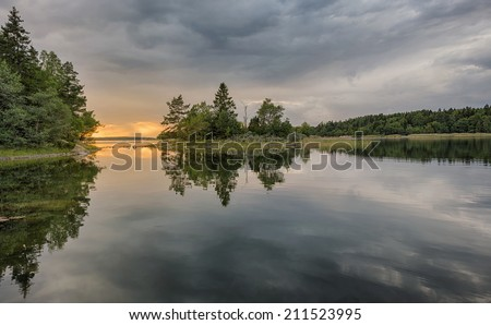 Forest landscape at coast mirrored in water during sunset. Grisslehamn, Sweden - stock photo