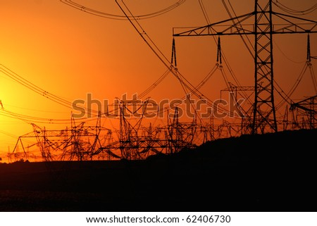forest of transmission towers over horizon during sunset - stock photo