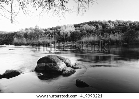 Forest river at sunset. Beautiful summer nature landscape. Forest river with rock stone and water cascade. Calm river and blue sky. Amazing nature background with lake and forest. Black and white.