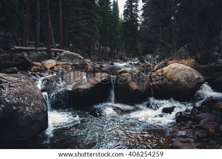 Forest river going through rocks and boulders. - stock photo