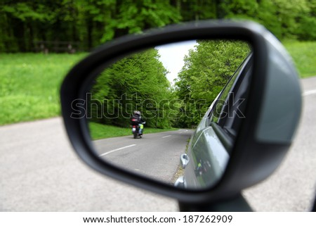 forest road reflection,  rearview car driving mirror view green forest road - stock photo