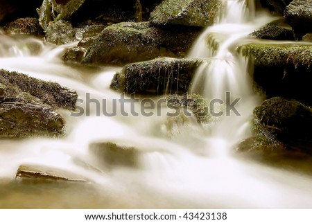 Forest stream flowed over the stones from a mountain slope. - stock photo
