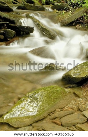 Forest stream flowing between the stones from the mountain slope. - stock photo