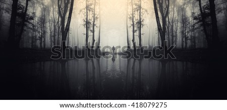 forest with reflection in lake and man silhouette