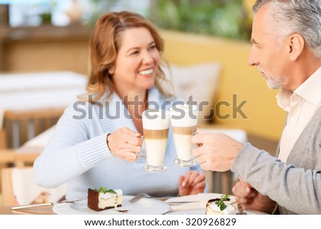 Forever together. Loving nice couple drinking coffee and eating cake while having tasty dinner in the cafe - stock photo