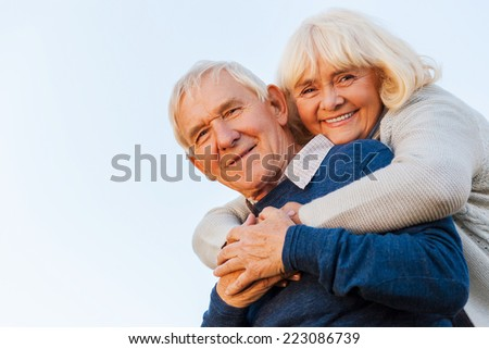 Forever young. Low angle view of happy senior couple bonding to each other and smiling with blue sky as background - stock photo