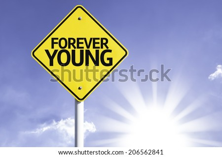 Forever Young road sign with sun background  - stock photo