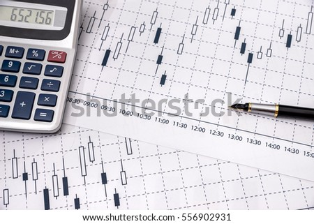 forex candlestick graph with calculator and pen.