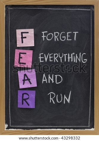 forget everything and run - FEAR acronym, shutting down or panic response concept, white chalk handwriting and sticky notes on blackboard