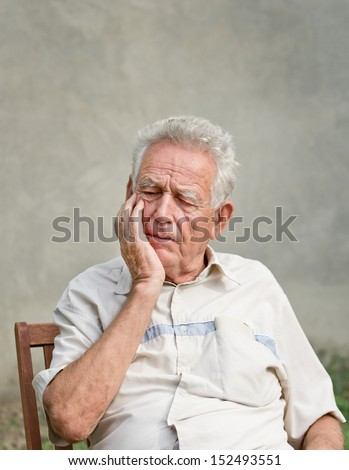 Forgetful old man holds hand on a face - stock photo