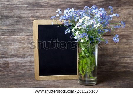 Forgetmenot flowers in vase on a wooden background - stock photo