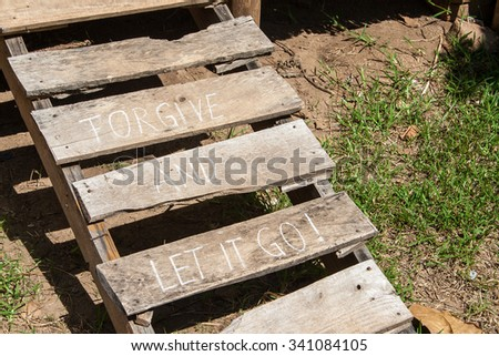 Forgive and let it go. Creative motivation concept written on wooden stairs. - stock photo