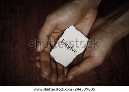Forgive stone block in hands with dark background. - stock photo