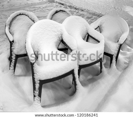Forgotten chairs after a snowfall in Les Deux Alps - France - stock photo