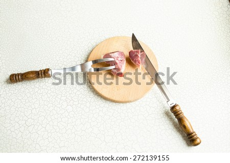 Fork and a large knife for cutting meat or ham are on the cutting boar. Cutting ham or smoked meat. - stock photo
