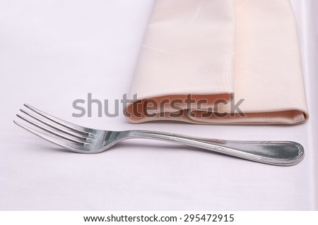 Fork and a napkin on a light table. Vintage effect and tone applied - stock photo