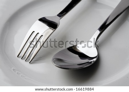 Fork and a spoon on a plate - stock photo