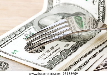 Fork and dollars on the wood table