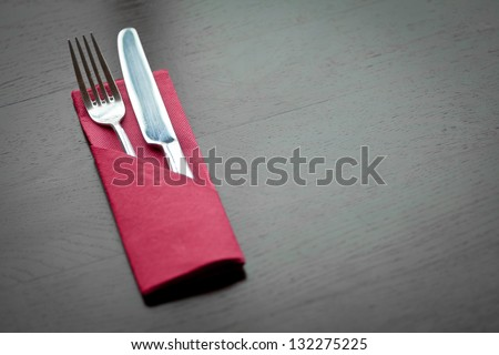 Fork and knife and a napkin on a table - stock photo
