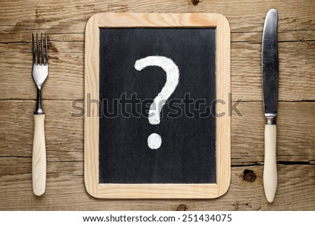 Fork and knife and question mark on blackboard - stock photo