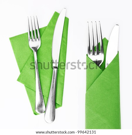 Fork and knife in a green cloth isolated on white - stock photo