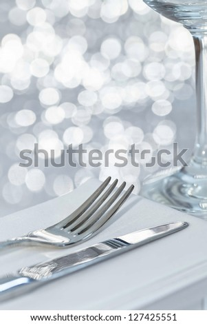 Fork and knife in elegant table setting with festive background - stock photo