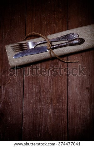 Fork and knife in napkin on wooden background. Toned.