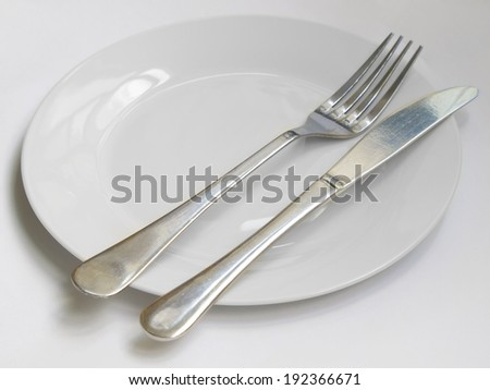 Fork and knife lie on white plate  - stock photo
