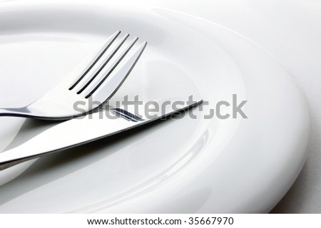 fork and knife lie on white plate