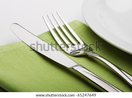 fork and knife on a green napkin with plate. - stock photo