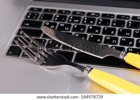 Fork and knife on computer keyboard close up - stock photo