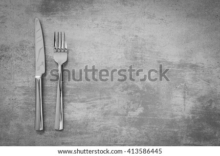 Fork and knife on grunge concrete background