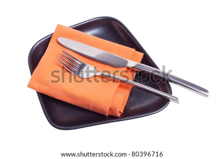 fork and knife on orange napkin and black plate isolated white - stock photo