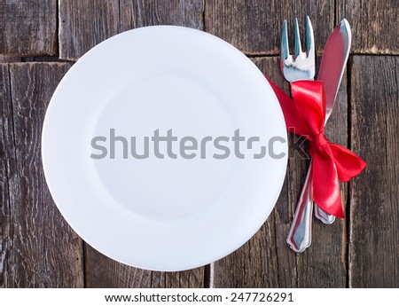 fork and knife on plate and on a table - stock photo