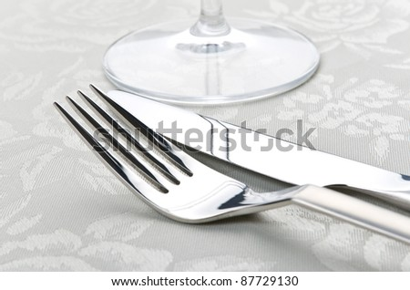 Fork and knife on table with white tablecloth.