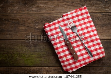 fork and knife on tablecloth on wooden - stock photo