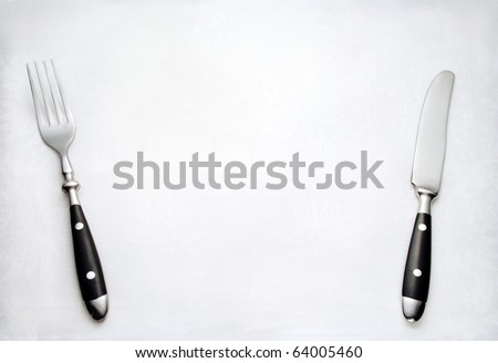 Fork and knife on white cloth - stock photo