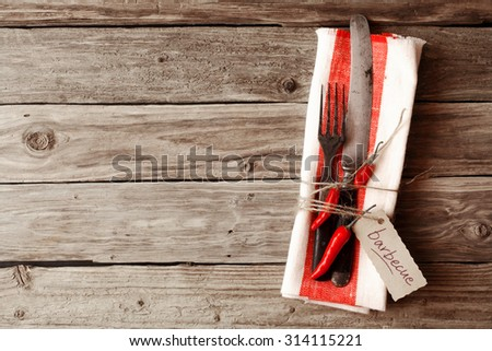 Fork and Knife Utensils on a Napkin with Red Chili Pepper and Barbecue Tag, Placed on Wooden Table with Copy Space. - stock photo