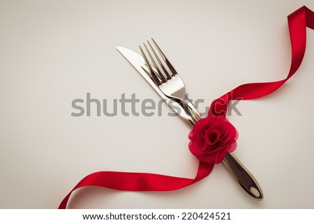 Fork and knife with decorative ribbon and rose. - stock photo