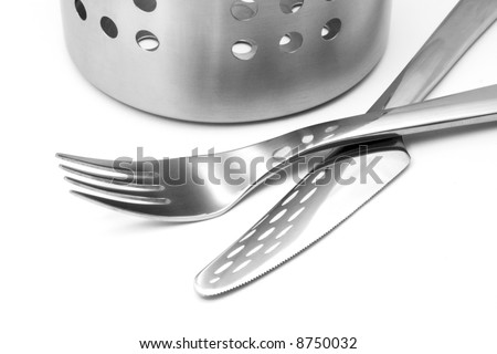 Fork and knife with the reflection of perforated cutlery stand. Isolated on white. - stock photo