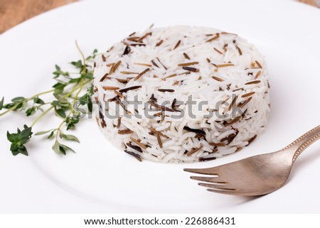 Fork and mixed cooked rice with thyme on white plate. Basmati and wild rice mix. - stock photo