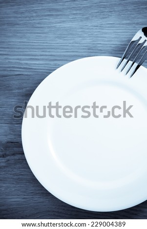 fork and plate at cutting wooden board