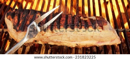 Fork and Pork Brisket on Hot BBQ Grill. Fire Flames in Background. You can see more grilled food, fire flames in my public set. - stock photo